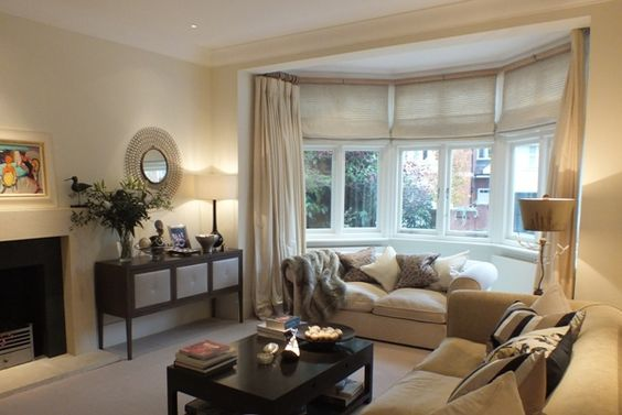 Beige living room with dress curtains design by sarah - Living room with bay window ...