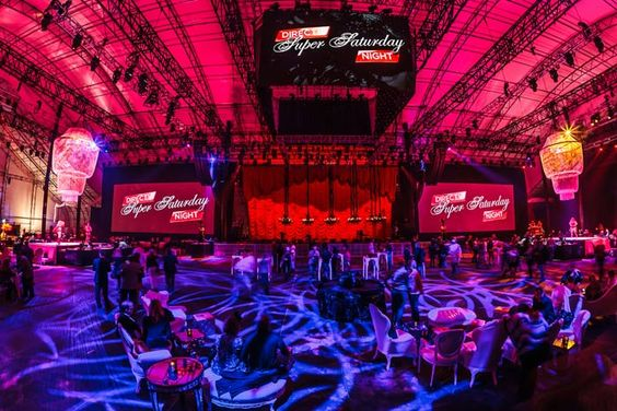 Producers had just four hours to convert the Celebrity Beach Bowl into a concert and lounge venue for DirecTV's Super Saturday Night. The tent rigging was built to allow the ceiling to hold as much as 100,000 pounds of equipment and decor. Two massive chandeliers balanced out the JumboTron, which concealed 15 smaller chandeliers during the touch football game