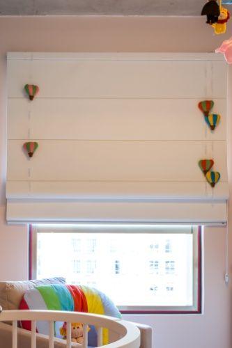 Os balões de feltro --presos a fios de nylon na persiana romana-- reforçam a atmosfera lúdica deste quarto de bebê, assinado pela By Arq