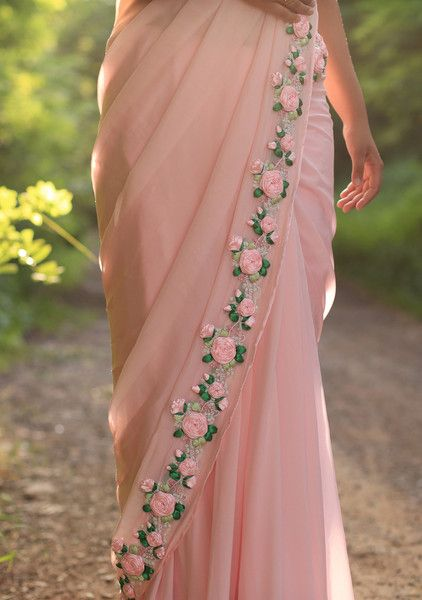 PRODUCT DESCRIPTION: Featuring a balmy baby pink pure chiffon saree with beautifully embroidered satin pink rose vines along the edges. It is embellished with French knots and glistening pink pearls. It comes with an unstitched raw silk blouse piece with baby pink rose buds and an unstitched matching satin petticoat fabric.  NOTES: Colours may appear slightly different due to photography lighting conditions and your monitor display settings.  SHIPPING/DELIVERY: This product will be shipped t...