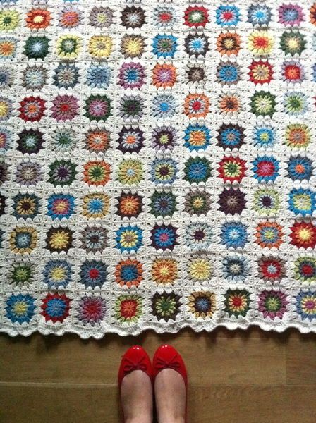 Crochet granny-square blanket with white borders...looks like a patchwork quilt but no sewing involved.