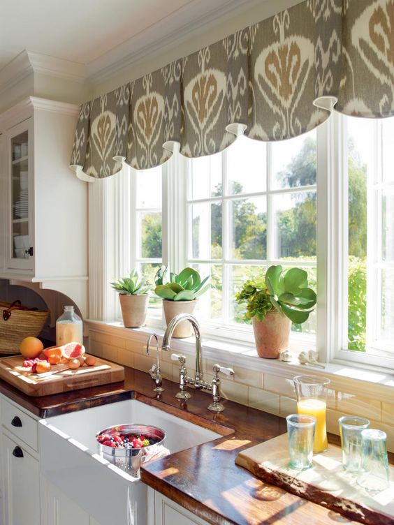 """In a kitchen with simple style and a mostly white color palette, a splash of pattern can add personality. """"Help frame a beautiful view with a valance mounted above the window. This ikat-patterned fabric, Bansuri in Slate, has a rich neutral that adds interest to the solid white cabinets,"""" says the manufacturer."""
