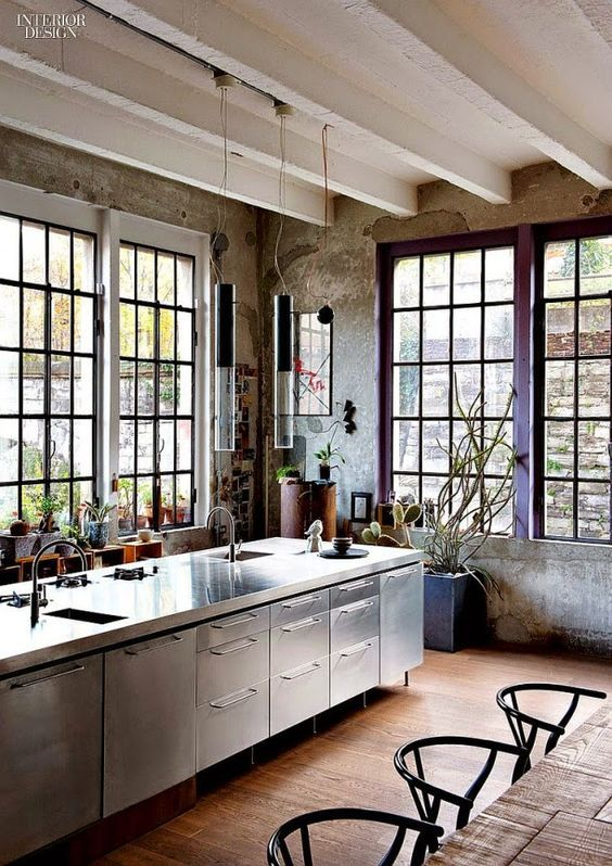 Black steel windows, stainless steel cabinets, and concrete in a lofty industrial farmhouse style kitchen. #industrialfarmhouse