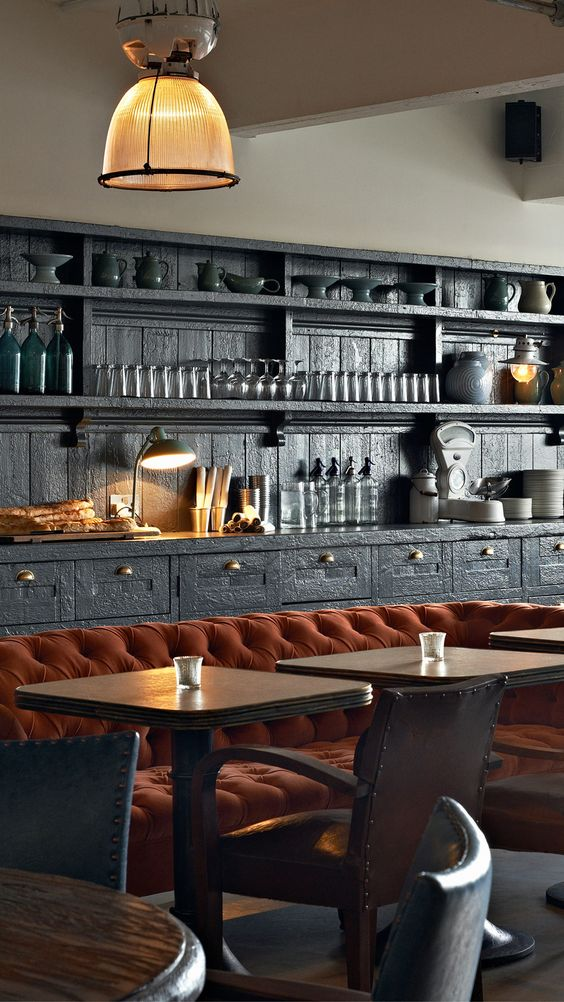 Dark gray cabinets with orange tufted banquette in a London Restaurant