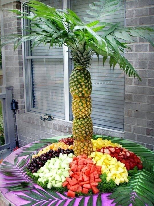 Edible Flower Arrangement in the shape of an exotic palm tree using pineapples as the trunk. The beach is made up of a variety of rich coloured tropical fruit.: