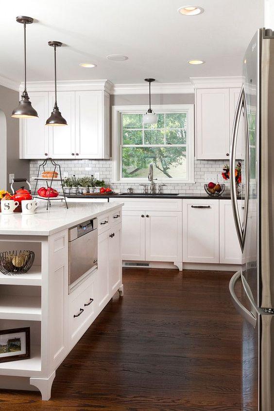 Классическая белая кухня: эстетика минимализма и 85 совершенных дизайнерских решений http://happymodern.ru/klassicheskaya-kuxnya-belaya-foto/ Белый фасад нижних кухонных шкафов и черная столешница – оформление основной рабочей зоны. Кухонный остров полностью оформлен материалами белого цвета и является многофункциональным