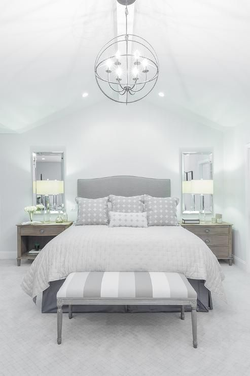 Beautiful grey bedroom features a cathedral ceiling accented with an iron sphere chandelier ...