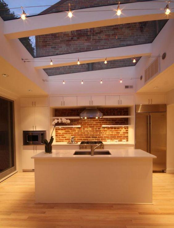 plafond lumineux, grandes verrières de toit et lampes électriques dans la cuisine