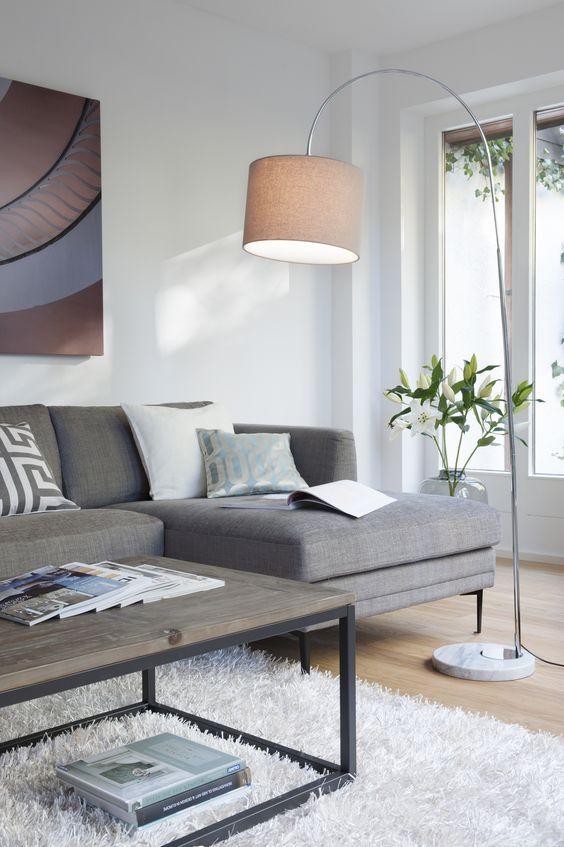 Elegant zurückhaltend: Relaxen auf Italienisch geht so: graues Ecksofa mit grazilen Metallbeinen, dazu eine schicke Bogenstehleuchte, ein schlichter, heller Flokati-Teppich und Moderne Architektur als Kunst an der Wand.