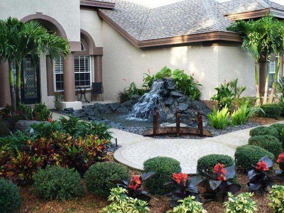 jardin moderne avec cascade, allée en dalles de pierre, buis boules et plantes vertes
