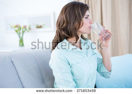 Thoughtful woman drinking a glass of water at home in the living room