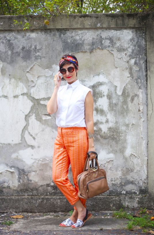 calça laranja, camisa branca e complementos estampados e coloridos