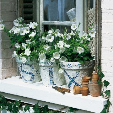 Pots de fleurs en terre ornés de mosaïque d'assiettes cassées avec le chiffre de la maison en toutes lettres