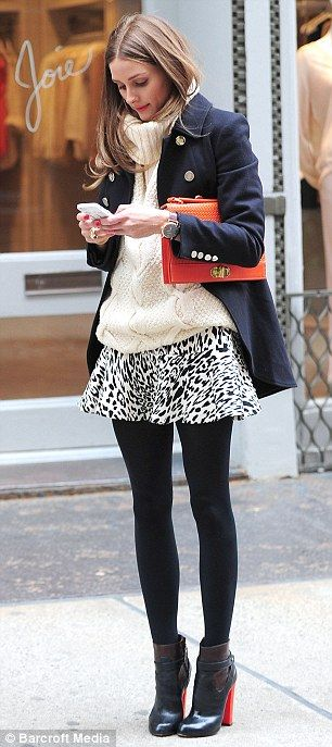 Olivia Palermo fought off the winter weather in NYC in a chunky white knit sweater, animal-print skirt, black booties and a double breasted coat. She completed the look with a bright orange clutch by Olivia + Joy.