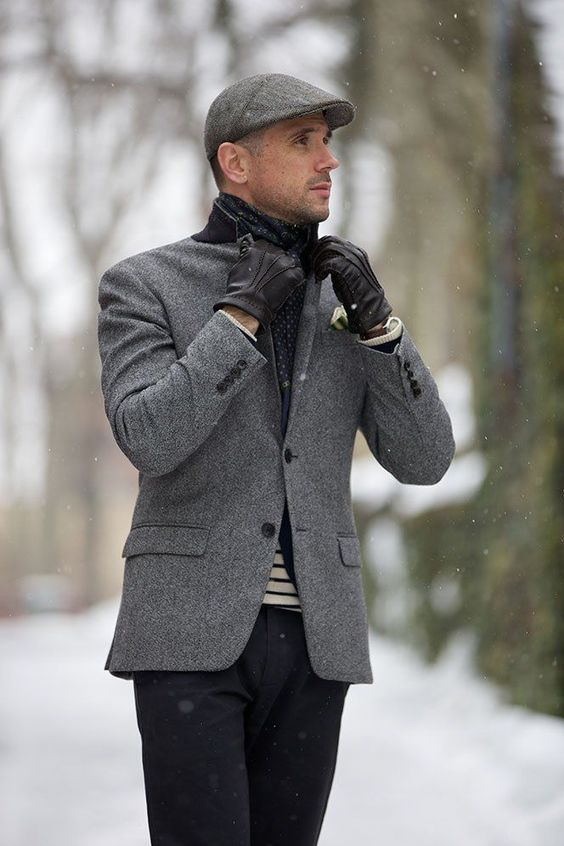 Stand out among other stylish civilians in a grey wool blazer jacket and black chinos. Shop this look on Lookastic: https://lookastic.com/men/looks/blazer-crew-neck-sweater-chinos/1419 — Black Leather Gloves — Navy Polka Dot Scarf — Black Chinos — Grey Flat Cap — Grey Wool Blazer — White and Navy Horizontal Striped Crew-neck Sweater