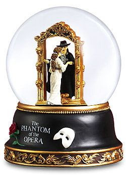 "Phantom of the Opera Snow Globe Enjoy your memories over and over again with an official snow globe from the classic musical. Millions have been transported into the mysterious world of the Paris Opera House, making this musical the longest running show on Broadway! Take yourself or someone you love on this journey into love and obsession with our charming Opera water globe. Plays the classic song from the musical, ""Music of the Night."" Measures 5"" L x 5"" W x 6"" H"
