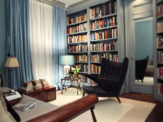 A soft blue is used on the walls, trim, door and curtains of this small home library along with a mirror on the back of the door to make the space feel larger.