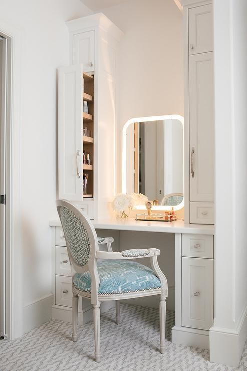 A Curved Light Vanity Mirror Is Flanked By White Pull Out Cabinets