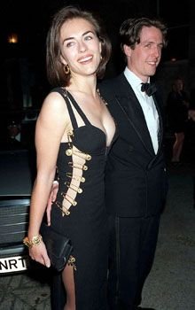 """Liz Hurley makes her debut as 'Hugh's Girlfriend' in a shocking safety pin dress by Versace at the 1994 premiere of """"Four Weddings and a Funeral""""."""