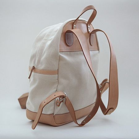 This durable compact Leather-Trimmed Canvas Backpack features a rugged, masculine design.  Leather trimmings throughout in tan. Single leather carry handle at top. Bottom leather keep the backpack in shape. Leather Reinforcing plate and adjustable leather shoulder straps at back.  Top zipper ...