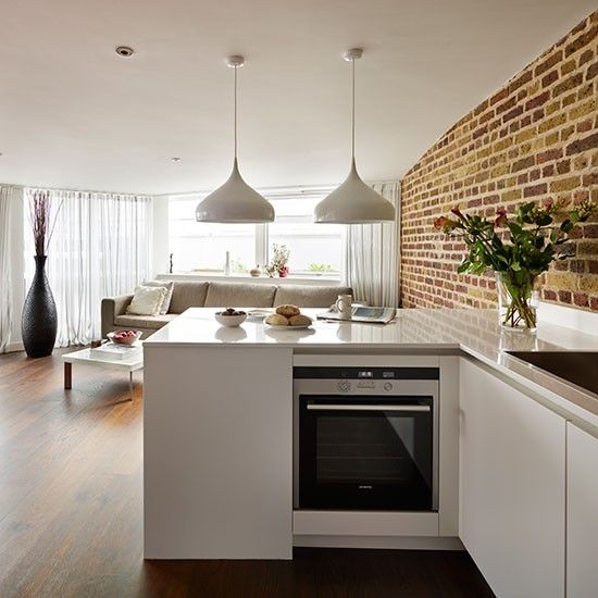 White open-plan kitchen with brick wall  White worktops and units can appear clinical in the wrong setting, but here they look wonderful set against the warm brick walls and dark wood floor - loving the combo of bare brick wall, white and dark floor