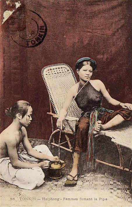 Femmes Fumant La Pipe - 1906Northern Vietnamese woman from Haiphong with maidservant smoking pipe. Studio photography for postal card