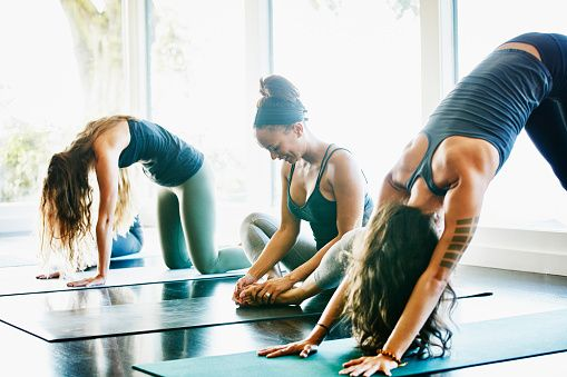 Group of women stretching before yoga class in studio: