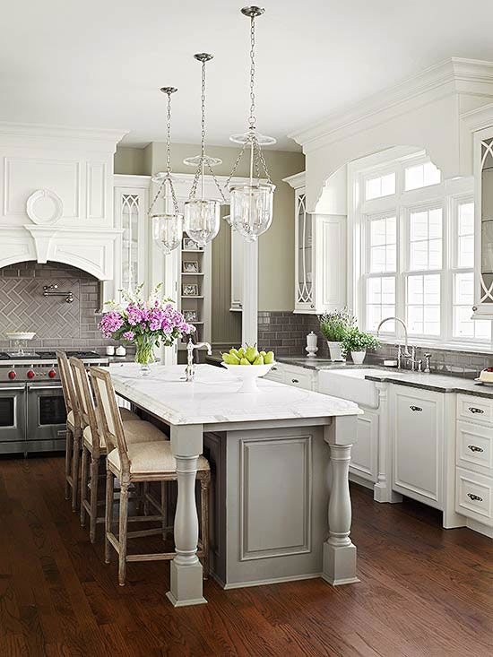 American Classic kitchen. Elegant millwork and furniture-like details give this new kitchen the spirit of a historic home. A grand and gracious gray island is at the heart of this kitchen, while white exterior cabinets and slab granite lighten the room's top half.