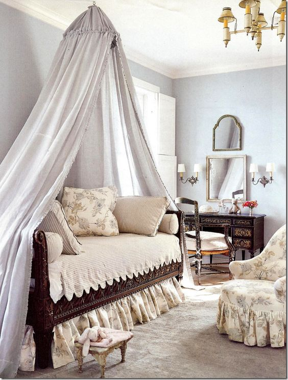 Bedroom designed by Jane Moore uses dark furniture and fixtures with light walls and linens.