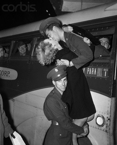"""Soldier Holds Up A Girl To Kiss Soldier.  Original caption:12/7/1941-New York, NY: A soldier's girl """"Kisses the boy goodbye"""" in a 34th Street bus terminal, while another soldier cooperates by holding her up to reach him. Picture taken just before bus load of Army men left, Dec. 7, when their leaves were terminated by the worsening situation in the Pacific, where Japanese planes bombed U.S. defense bases."""