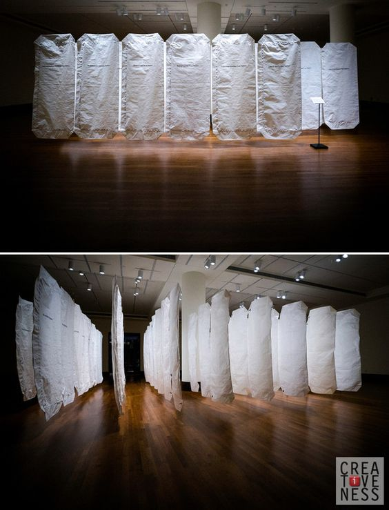"""Week 40 - Covering my stomach, I approached the installation. It was my face that I covered when I realized the silent apparitions were not abstracted sheets of fabric but body bags, each tagged with the name of a tribe or nation. The tears were swift and sudden. Bonnie Devine's """"Manitoba"""" had touched me before the description had been read. Later, reading that it was not an old cruelty but a fresh offence that was being evoked further saddened me, giving my gut an extra twist."""