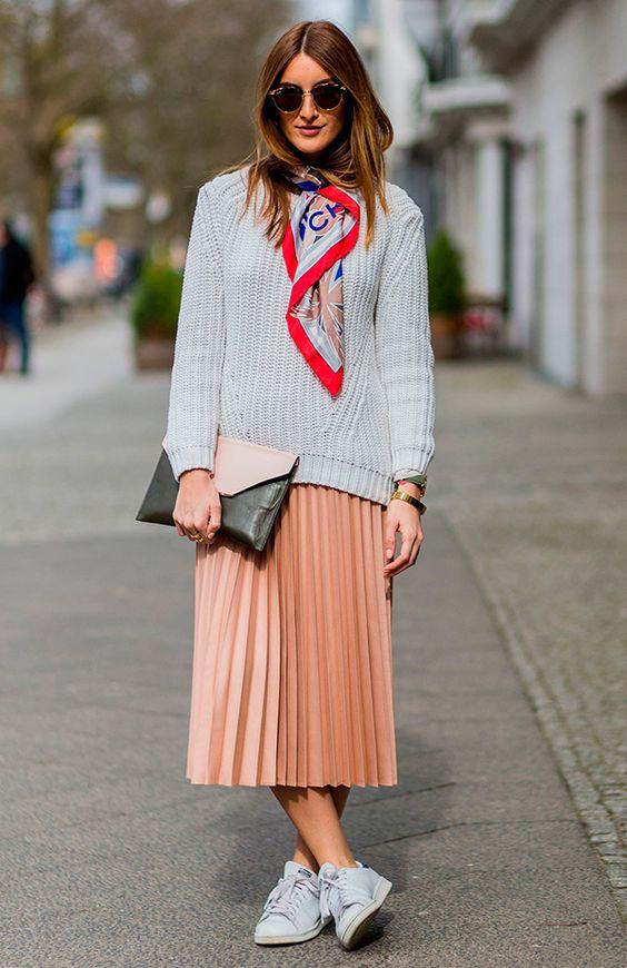 Mulher posa com look comfy usando tricot cinza, saia midi plissada, tênis branco e finaliza o look com um lenço clássico amarrado no pescoço: