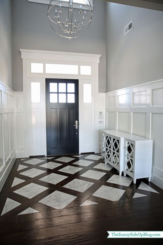 could do this look in foyer but with wood look tile as the dividing pieces not true wood would have to find a wood tile close to the color of the wood floor we want: