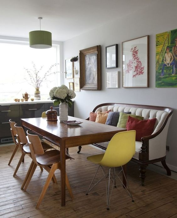 dining area in modern home with yellow vintage chair and settee