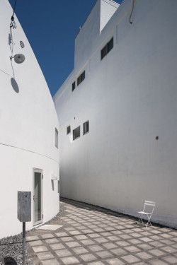 Y House is a minimalist house located in Hiroshima, Japan, designed by Hideyuki Nakayama Architects. The home is two-storys with one side that is completely grey and practically windowless, and the other a curved, white wall that matches the color of the adjacent building. (3)