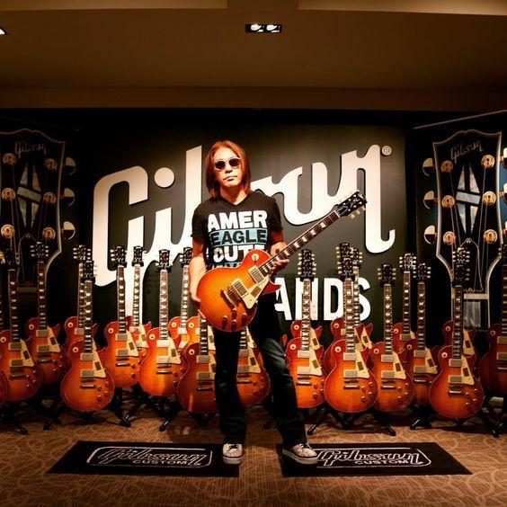たくさんのギターの前に立つ松本孝弘