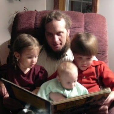 Amish father reading to children