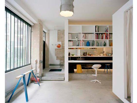 Cemento e pareti grezze. Sugli scaffali sopra il piano della cucina, i vasi della serie Domestic Landscape. Design di Victoria Wilmotte anche per il cavalletto, parte di un tavolo prodotto su ordinazione.