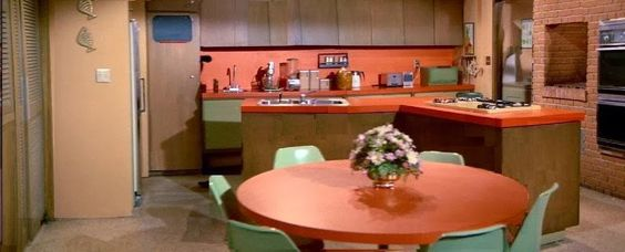 The Brady Bunch kitchen with orange Formica counters and tabletop, green atomic chairs, smoky-teak wood cabinets.: