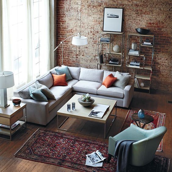 An Enchanting Living Room Design With Red Brick Wall Design With Modern  Grey Sofa And Orange Cushion With Red Ethnique Rug And Simply Wooden Shelf U2026