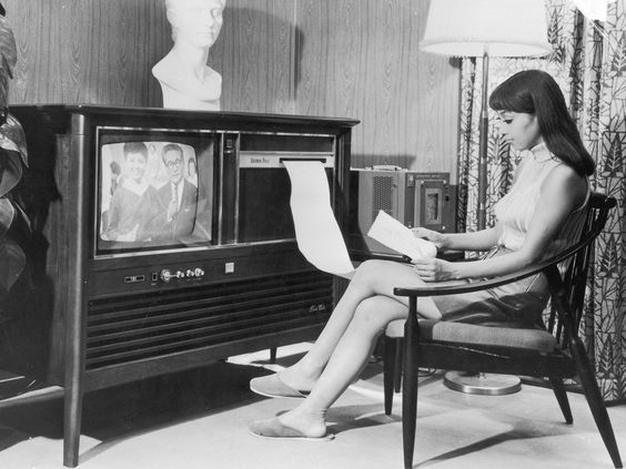 Flat screen televisions are decidedly minimalist compared to their forerunners. In the 1960s a television was not just a television. Frequently, it was a piece of furniture that incorporated some other fixture or object, such as a lamp, bureau or cabinet. Taken in 1969 this image depicts a woman reading a message from her combination TV-fax machine.