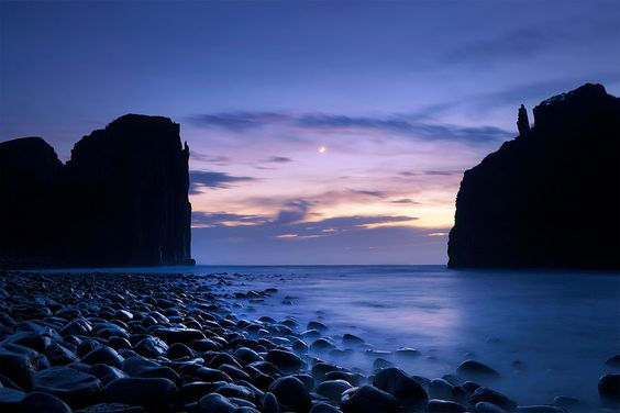 """The Gateway"", Hole in the Wall, Wild Coast, South Africa (photograph by Hougaard Malan.) ""This gap between the hole in the wall and  the cliff it used to be a part of looks like a gateway to the Indian Ocean in a medieval port. The crescent moon rising in a soft glow amongst a dark blue sky over the blurred water adds to the atmosphere of something mystical."""
