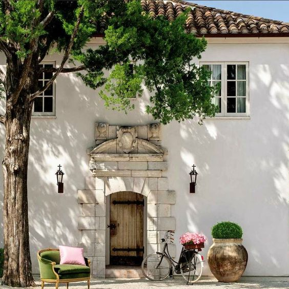 French Farmhouse style stucco exterior and tile roof is the guest house in Houston of Annette Schatte. Breathtaking architecture and setting! #Frenchfarmhouse #FrenchCountry #houseideas #homeexterior #houseexterior #housegoals #dreamhomes #stucco #tileroof #limestone #curbappeal #frontdoor #homeideas