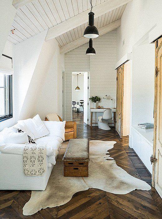 Leanne Ford designed living area with herringbone wood floor, hide rug, white sofa, wood vintage sliding doors, beadboard ceiling, and black barn style lighting. #beadboard #barndoor #hide #leannford #boho