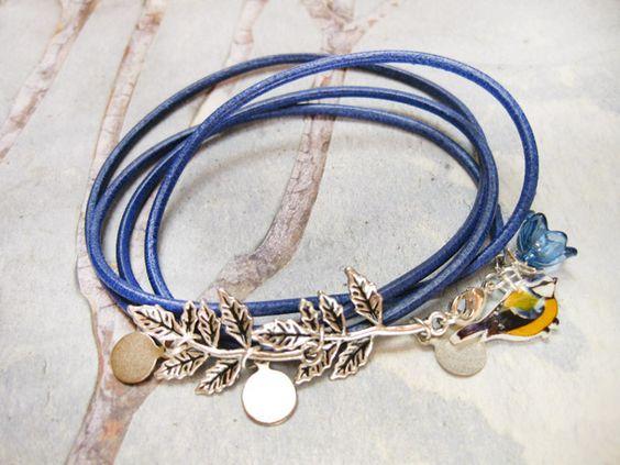 Schönes Wickelarmband aus dunkelblauem Leder mit einer kleinen Meise.  Zwei silberne Zweige, silberne Metallblättchen und eine blaue Blume verschön...