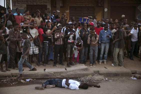 Bystanders stand around the body of a suspected Ebola victim lying in a street in the town of Koidu, Kono district in Eastern Sierra Leone, December 18, 2014. REUTERS/Baz Ratner