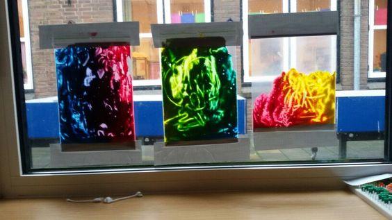 Kleuren mengen op het raam. Verf in een plastic zak. Vasthouden met tape en schilderen m.b.v een wattenstaafje.