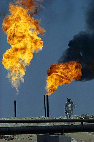 SAUDI ARABIA  Industry Flaming gas on oil field with man standing behind pipe in…