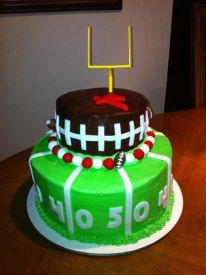 Football cake with blue and pink helmets on top with just the green bottom tier.