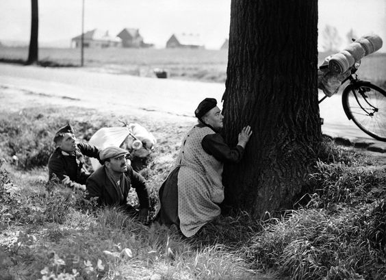 A woman, fleeing from her home with the few possessions she can carry, takes cover behind a tree by the roadside, somewhere in Belgium, on May 18, 1940, during an aerial attack by Nazi planes. Her bicycle, with her belongings tied to it, rests against the tree, to which she clings for protection. (AP Photo)